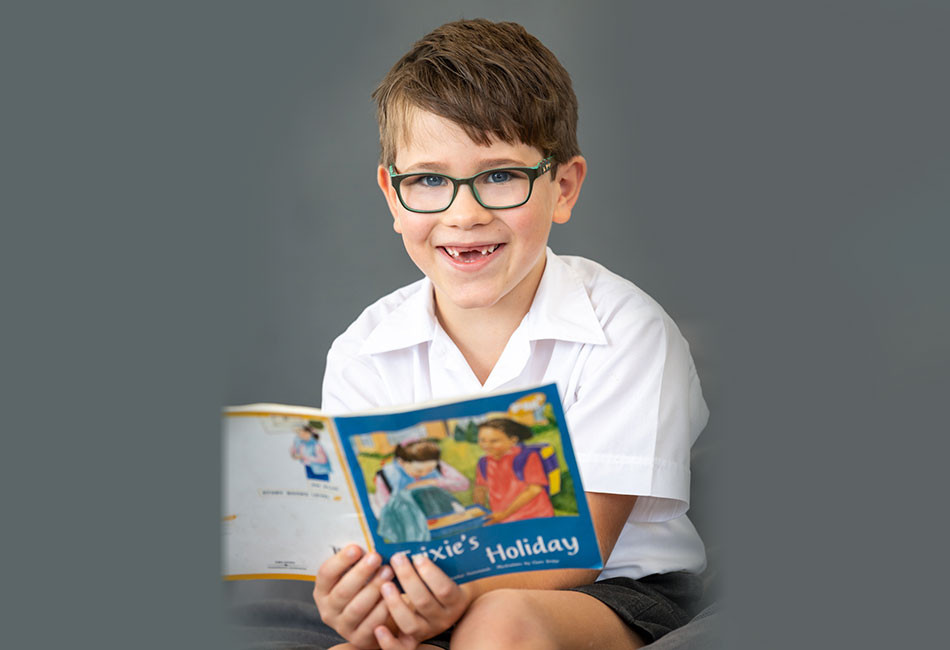 A primary school boy reads a book